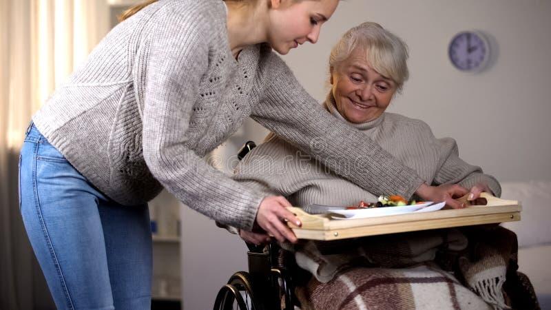 Cena servente volontaria femminile alla donna anziana handicappata, cura dell'anziano, aiuto fotografia stock libera da diritti