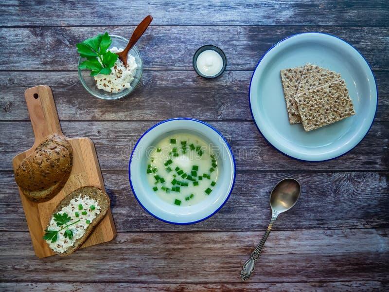 Cena su una tavola di legno rustica: una ciotola di minestra di verdura con le cipolle verdi, il pane intero su un tagliere ed i  fotografia stock