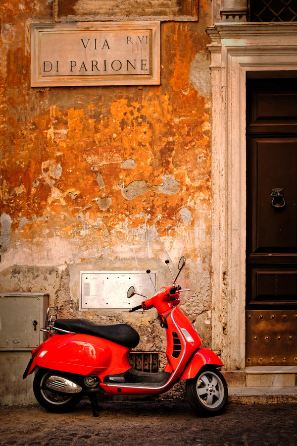 Cena típica com um 'trotinette' vermelho em uma rua central estreita de Roma fotografia de stock royalty free