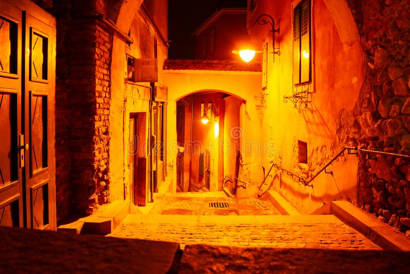 Cena urbana da noite de uma excursão do fantasma Luzes de rua vermelhas/amarelas em uma passagem estreita com escadas Nenhuns pov imagens de stock royalty free