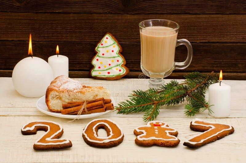 Cena y pan de jengibre de la Navidad, empanada spruce de la rama, de la vela, del capuchino y de manzana en una tabla de madera imágenes de archivo libres de regalías