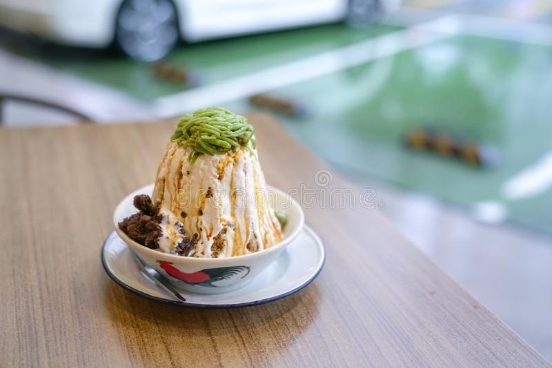 Cendol, an iced sweet dessert, very popular in Malaysia. Bowl of Cendol on a table. It an iced sweet dessert that contains green rice flour jelly, coconut milk royalty free stock image