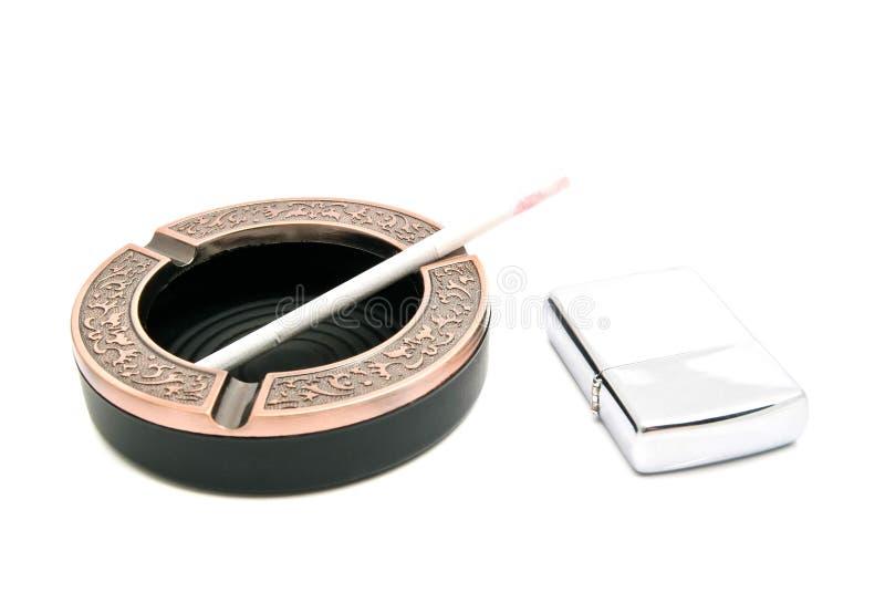 Cendrier avec la cigarette et l'allumeur image stock