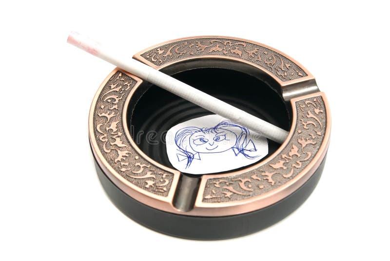 Cendrier avec la cigarette et le portrait de l'enfant photographie stock