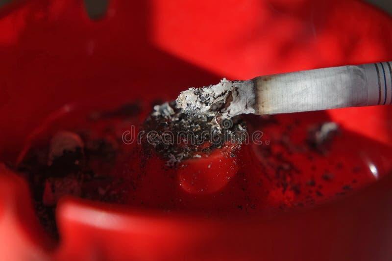Cendrier et cigarette allumée images libres de droits