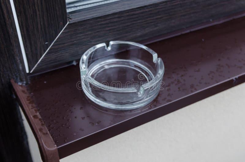 Cenicero de cristal en la tabla de madera fotos de archivo libres de regalías