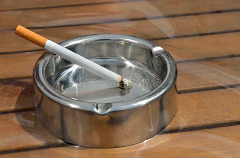 Cenicero del metal con un cigarrillo foto de archivo