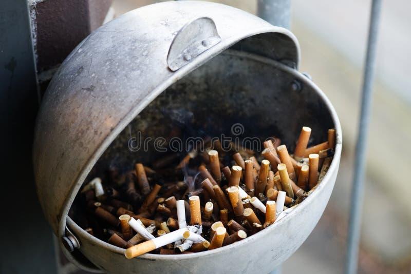Cenicero por completo de cigarrillos usados fotos de archivo libres de regalías