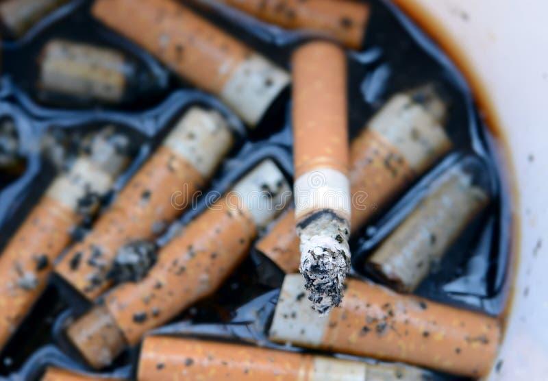 Cenicero por completo de extremos quemados cigarrillos fotografía de archivo