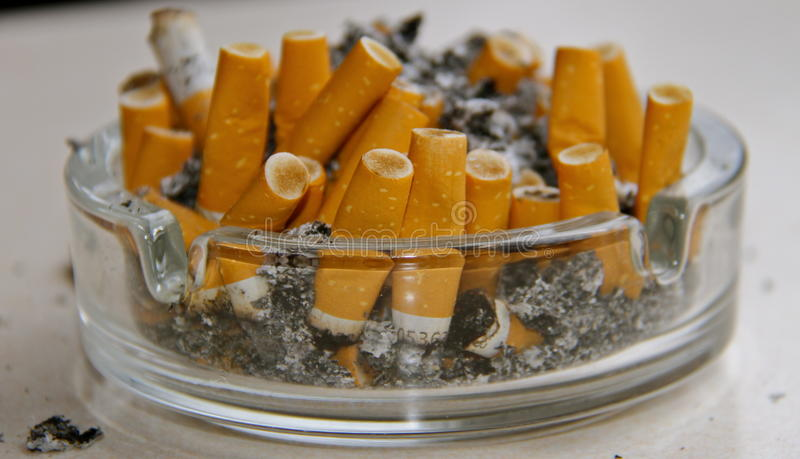 Cenicero por completo de los cigarrillos imagen de archivo libre de regalías
