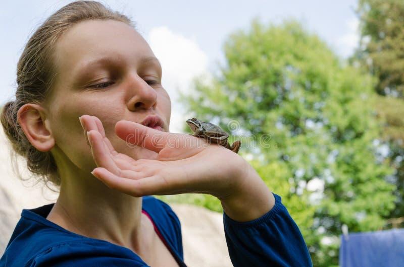 Cenicienta que besa la pequeña rana en la palma fotografía de archivo