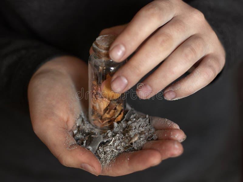 Ceniza en las palmas femeninas Burbuja con los pétalos color de rosa Memorias y un corazón quebrado foto de archivo libre de regalías