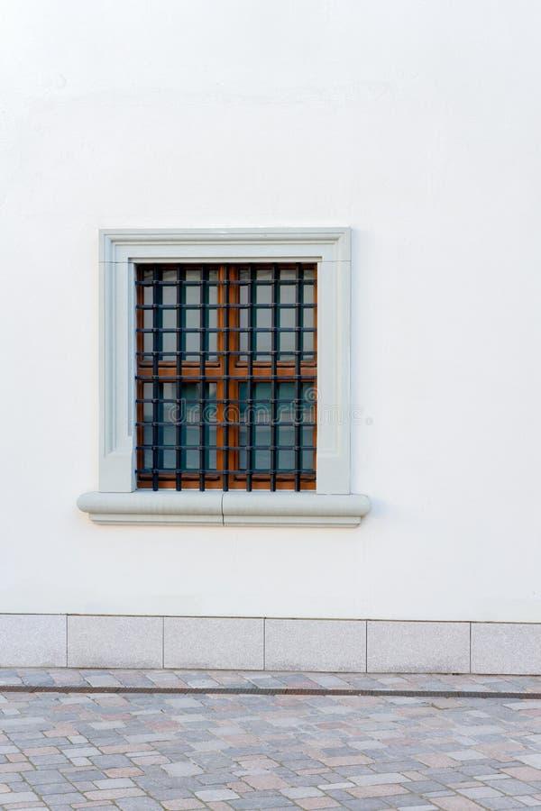 Cenni storici urbani Parete bianca con la piccola griglia del ferro e della finestra immagini stock