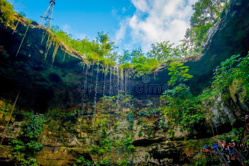 Cenote de Ik-Kil cerca de Chichen Itza, México El cenote precioso con aguas y la ejecución transparentes de la turquesa arraiga e fotografía de archivo