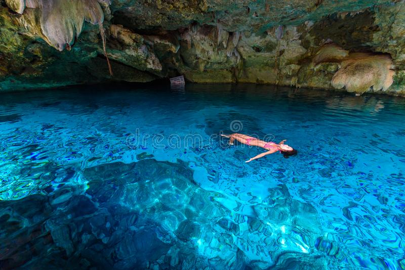 Cenote Dos Ojos in Quintana Roo, Mexico. People swimming and snorkeling in clear blue water. This cenote is located close to Tulum royalty free stock photo
