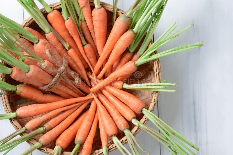 Cenoura fresca, cenoura de bebê na cesta no fundo de madeira branco imagens de stock