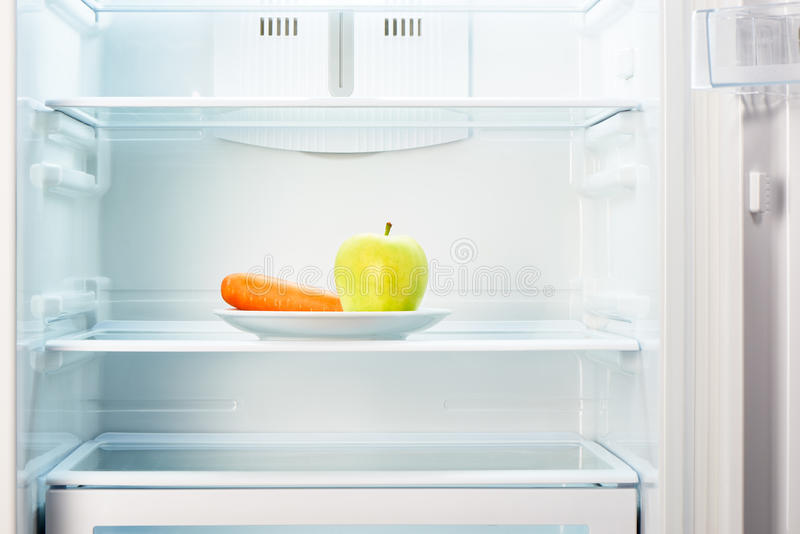 Cenoura verde da maçã e da laranja na placa branca no refrigerador vazio aberto imagens de stock royalty free