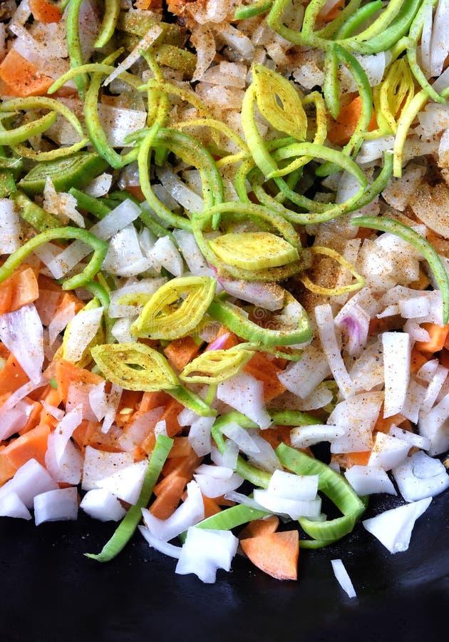 Cenouras, cebola, alho-porro e especiaria cortados no ferro fundido da cozinha como o fundo foto de stock