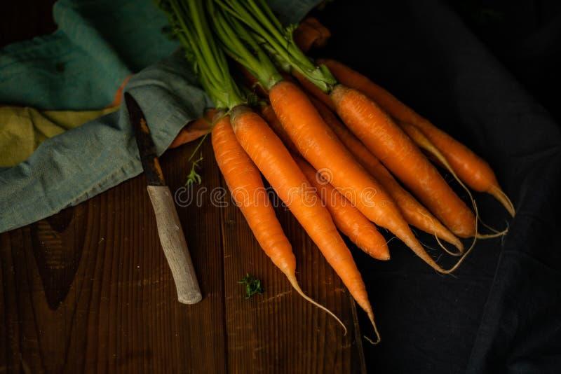 Cenouras com a faca no claro-escuro fotografia de stock