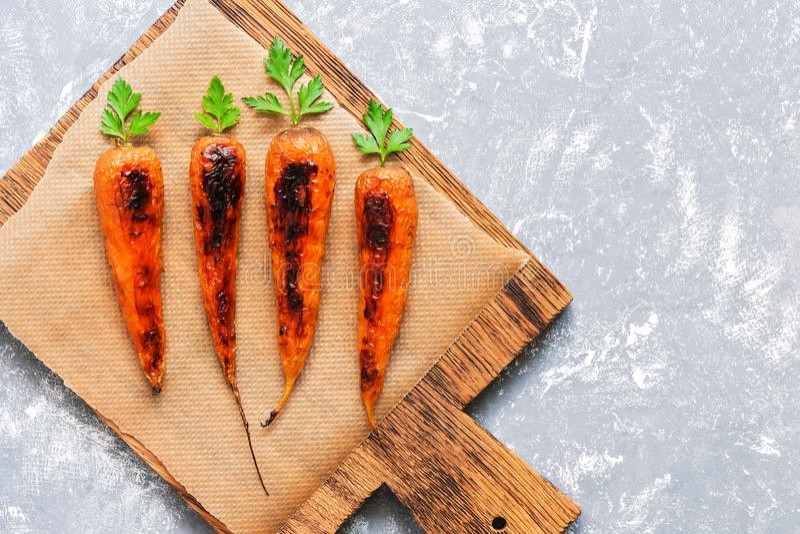 Cenouras cozidas com caudas verdes em uma placa de corte, fundo cinzento Alimento dietético do vegetariano Vista superior, config imagens de stock