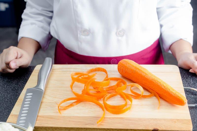 Cenouras da casca do cozinheiro chefe fotos de stock royalty free