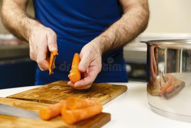 Cenouras da casca do homem imagem de stock
