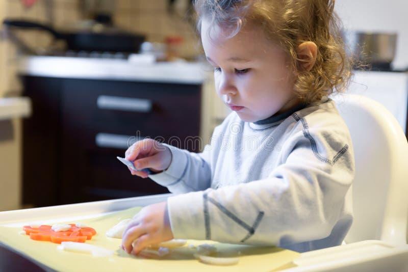 Cenouras e batatas dos cortes da criança na cozinha foto de stock royalty free