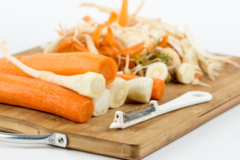 Cenouras e pastinaga descascadas na placa de madeira do corte imagens de stock royalty free