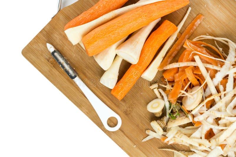 Cenouras e pastinaga descascadas na placa de madeira do corte fotografia de stock