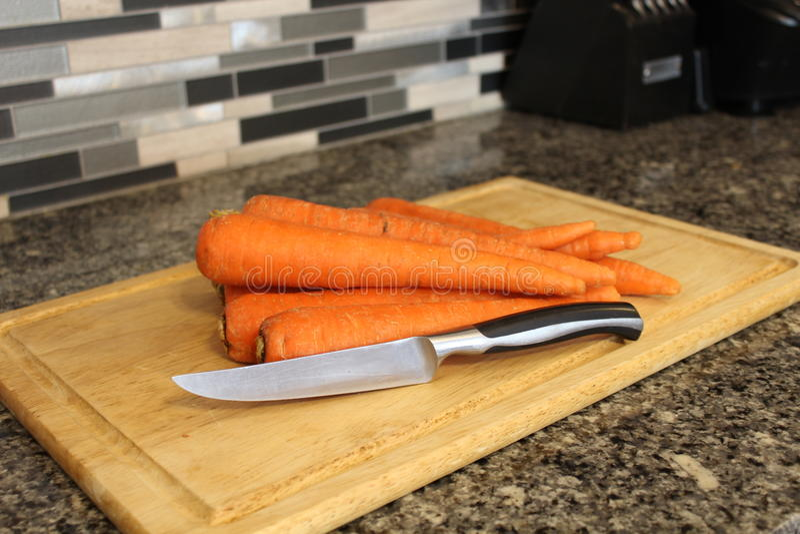 Cenouras e uma faca em uma placa de corte imagem de stock