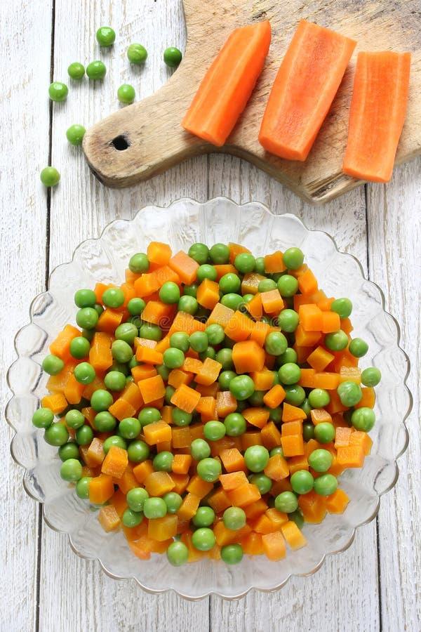 Cenouras fervidas com ervilhas verdes fotografia de stock