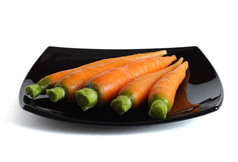 Cenouras frescas em um prato preto imagem de stock