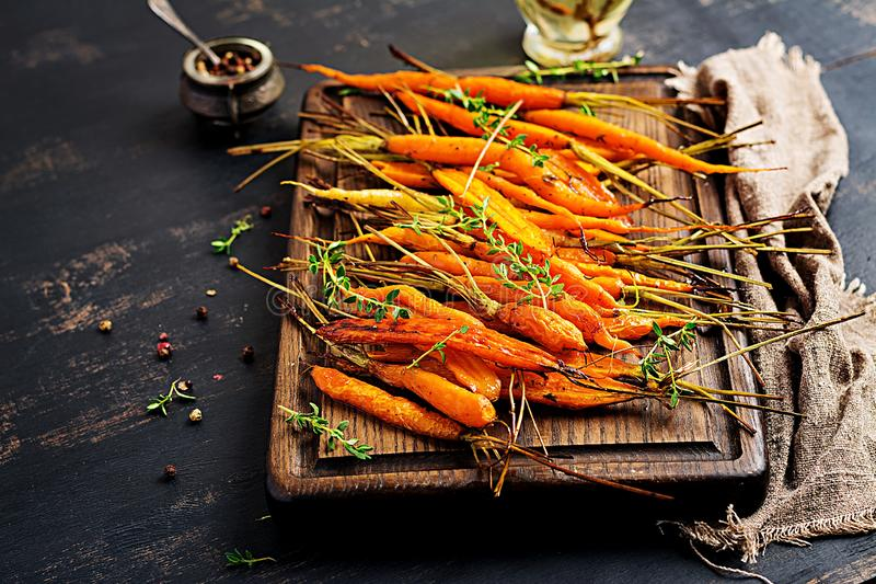 Cenouras orgânicas cozidas com tomilho, mel e limão O vegetariano orgânico foodBaked cenouras orgânicas com tomilho, mel e limão imagens de stock