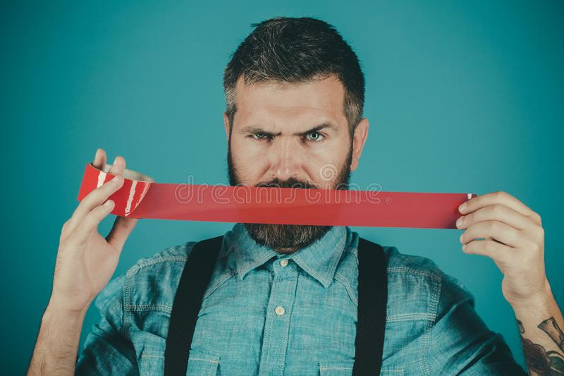 Censorship. Brutal bearded male. freedom of speech and press. International Human Right day. Mind control and propaganda. Man wrapping mouth by adhesive tape royalty free stock photos