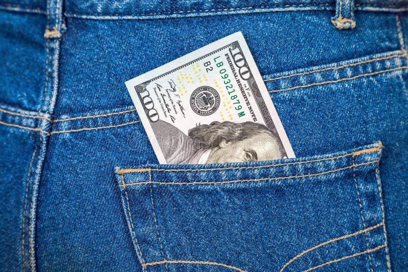 Cent billet d'un dollar collant hors de la poche de jeans photo stock
