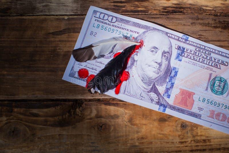Cent billets d'un dollar avec la plume dans la tête du président et du bl photo libre de droits