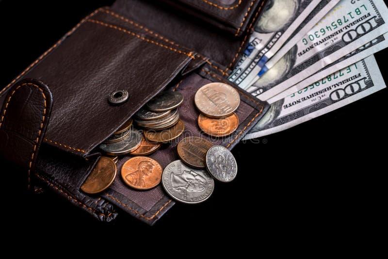 Cent billets d'un dollar dans la bourse en cuir foncée d'isolement photographie stock