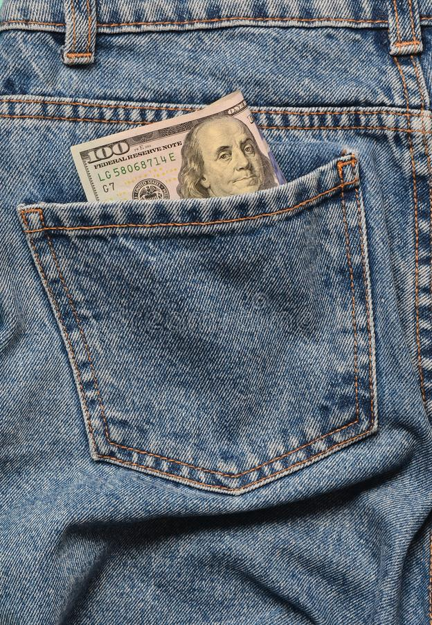 Cent billets d'un dollar dans la poche arrière des jeans fripés image libre de droits
