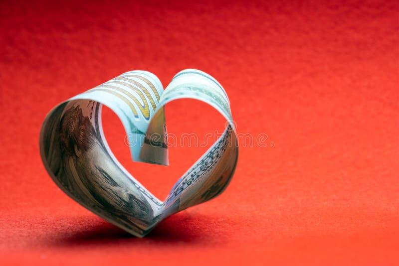Cent billets d'un dollar pliés sous forme de coeur sur un fond rouge Copiez l'espace Concept d'argent, d'amour et d'un cadeau pou photos stock