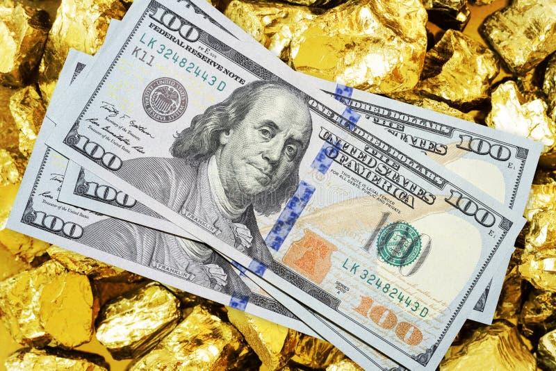Cent billets de banque du dollar sur la fin de mine d'or  Concept d'industrie minière avec les dollars et l'or photo stock