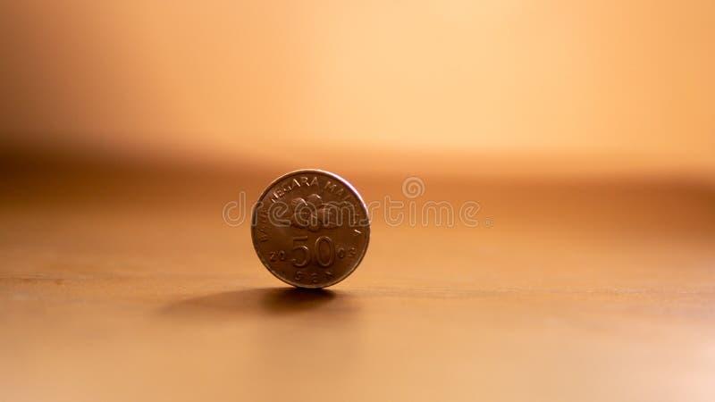 50-Cent-malaysische Münze auf braunem Holztisch stockfotografie