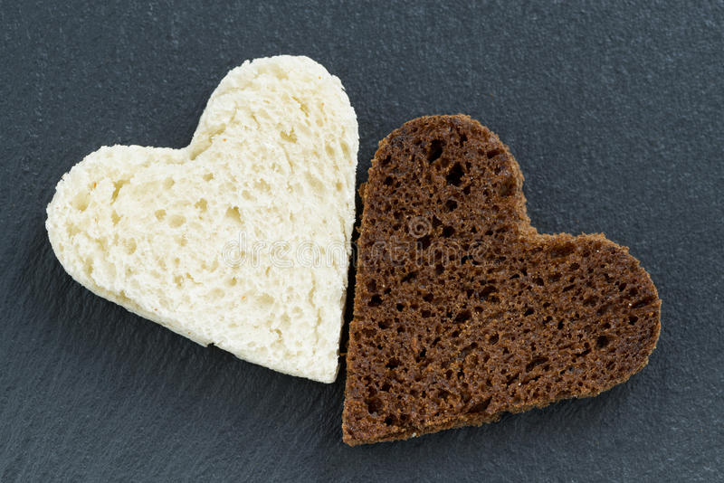 Centeio e pão branco brindados sob a forma do coração na obscuridade fotos de stock royalty free