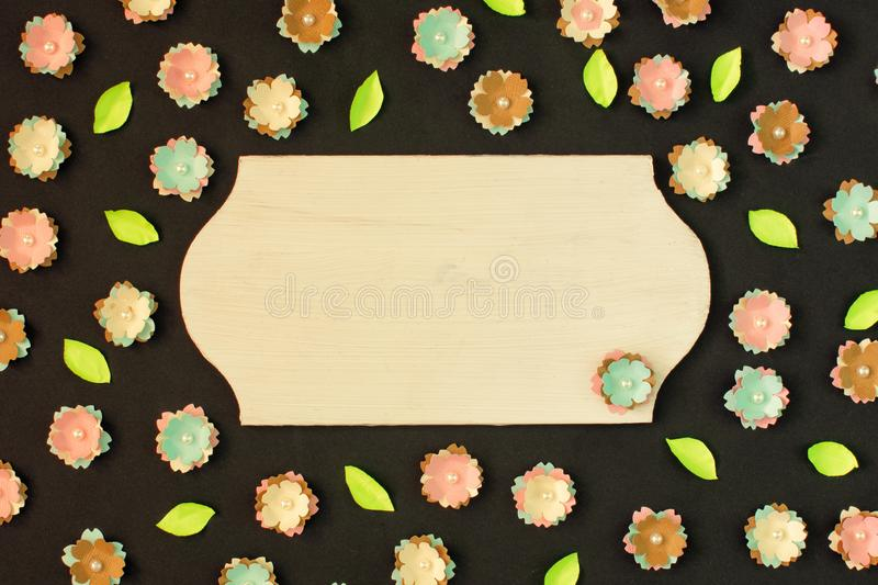 In the center of the black background is an empty plate with copy space. Small paper flowers scattered around. royalty free stock photo