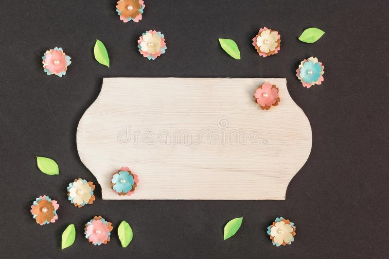 In the center of the black background is an empty wooden plate. Copy space. Near small paper flowers. stock images