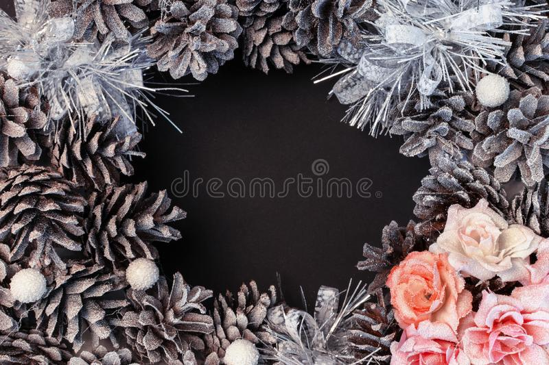 In the center of the black background is a place for an inscription, copy space. Around the frame of cones and flowers. royalty free stock image