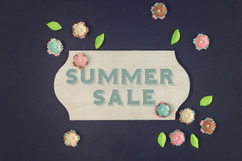 In the center of the black background is a sign, on which is the inscription Summer Sale. Around chaotically lie small royalty free stock image