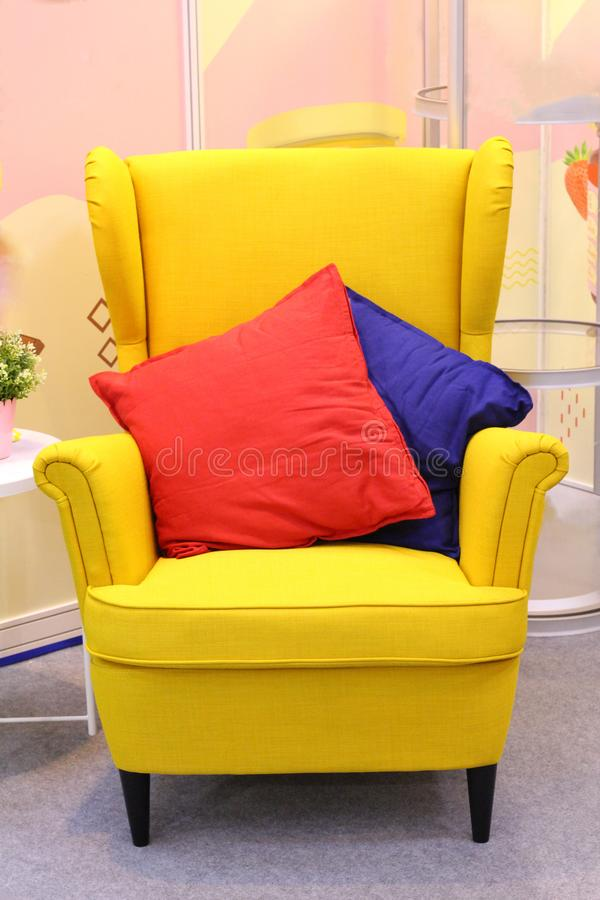 In the center is a bright yellow armchair, with two pillows on it - red and blue stock image