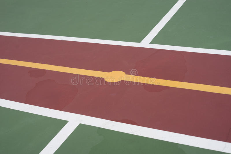Center of futsal field with green, red and yellow color, water flooding on a floor. Centre of futsal field with green, red and yellow color, water flooding on a royalty free stock photo