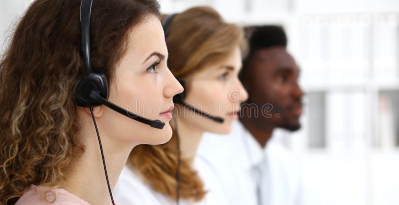 Center operatör för ett felanmälan Ung härlig brunettkvinna i hörlurar med mikrofon äganderätt för home tangent för affärsidé som royaltyfria bilder