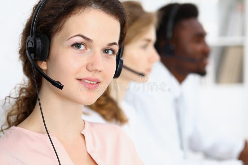 Center operatör för ett felanmälan Ung härlig brunettkvinna i hörlurar med mikrofon äganderätt för home tangent för affärsidé som royaltyfria foton